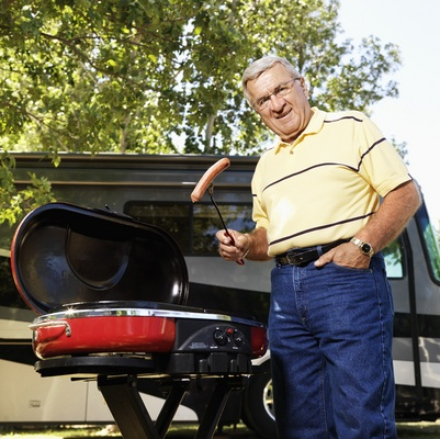 Man grilling hot dogs by SUV